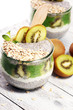 Leinwanddruck Bild - Healthy breakfast. chia pudding with kiwi and granola in glass on rustic background.