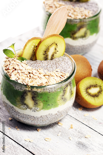 Leinwanddruck Bild Healthy breakfast. chia pudding with kiwi and granola in glass on rustic background.