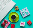 Cup of coffee with gift boxes and computer on blue background