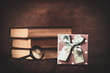 Books with loupe and gift box on wooden background. - 230318184