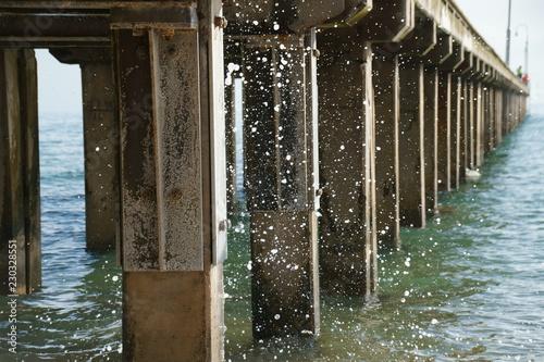 water splashing a pier at a beach in Victoria, Australia
