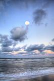 Moonset over the ocean at Vanderbilt Beach at sunset