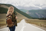 A woman with a backpack and a road stretching into the distance against the backdrop of mountains - 230362128