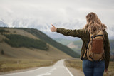 A woman with a backpack and a road stretching into the distance against the backdrop of mountains