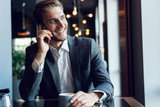 Handsome businessman talking on the phone during coffee break in a cafe. - 230366930