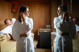 Young happy couple relaxing inside a sauna at spa resort hotel luxury - 230371780