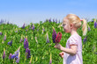 Leinwanddruck Bild - Mädchen pflückt Blumen auf einer Blumenwiese