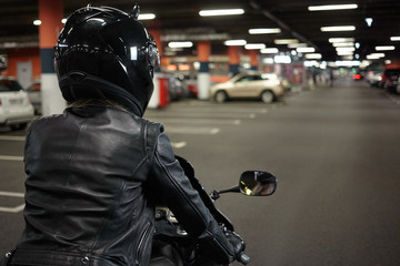 Isolated back view of female biker driving two wheeled sportbike along underground paking lot hallway, going to park her motorcycle after night ride. Motorcycling, extreme sports and lifestyle