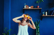 Young woman on a blue background holds a cut orange in her hands and laughs. Colour obsession concept.