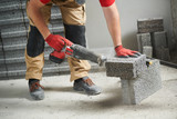 bricklayer cutting ceramsite concrete blockswith saw at walling - 230392556