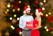 people, discount and holidays concept - happy couple in santa hats with red sale sign over christmas tree lights background