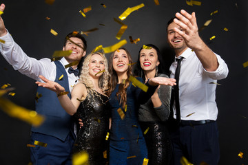 celebration, people and holidays concept - happy friends at party under golden confetti over black background