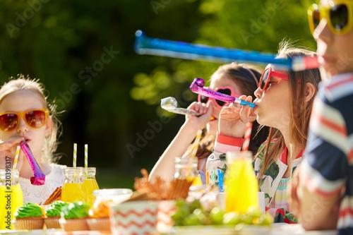 urodziny, dzieciństwo i uroczystości koncepcja - zbliżenie szczęśliwy dzieci dmuchanie rogi strony i zabawy w lecie