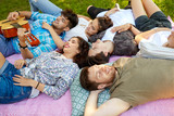 friendship, leisure and summer concept - group of happy smiling friends playing guitar and chilling on picnic blanket at summer park - 230398534