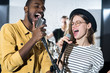 Waist up portrait of two young people enjoying singing with microphones during band performance on stage