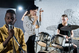 Portrait of contemporary music band performing on stage, focus on young woman singing to microphone, copy space - 230411371