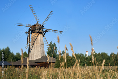 Leinwanddruck Bild Wooden windmill with ears of wheat growing in the field on the foreground