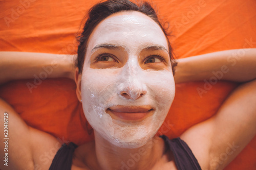 Leinwanddruck Bild Portrait of happy young beautiful smiling sporty woman with white facial clay mask relaxing on the bed - Beauty treatments for face, skin and body care, healthy lifestyle and love yourself concept