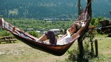 Girl sleeping in a hammock on the nature against the background of green mountains, slow motion - 230420144