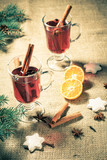 Glass of Christmas mulled wine with spices, orange and cookies on sackcloth - 230421178