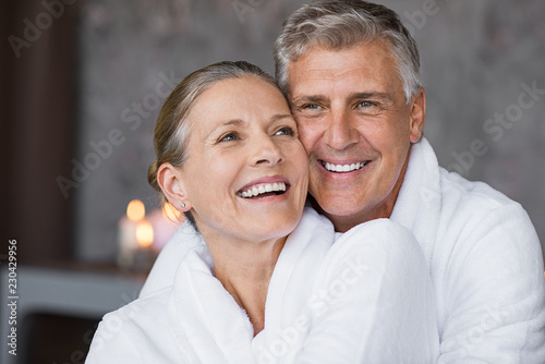 Leinwanddruck Bild Laughing senior couple embracing at spa