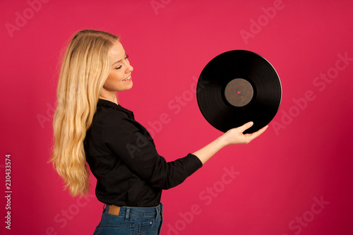 Beautiful young woman holding a vinyl in her hands as she listens to the music - 230433574