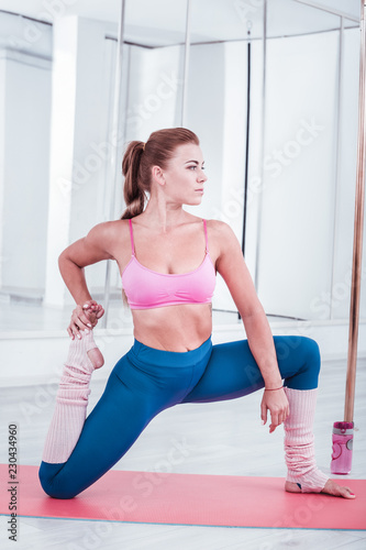 Before dancing. Professional experienced pole dancer feeling busy stretching her legs before dancing - 230434960