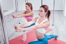 """Постер, картина, фотообои """"Dance studio. Two slim beautiful successful women visiting pole dance studio on their weekend together"""""""