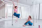 Teacher moving. Red-haired diligent inspired student of pole dance studio watching her teacher moving - 230436516