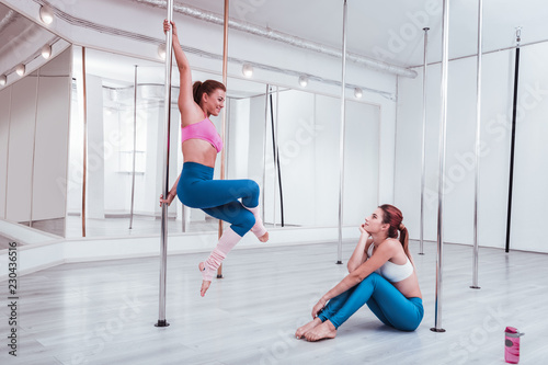 Teacher moving. Red-haired diligent inspired student of pole dance studio watching her teacher moving
