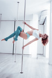 Wavy hair. Red-haired athletic pole dancer with wavy hair giving amazing master class to her clients - 230437964