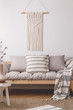 White handmade macrame above comfortable beige living room sofa with lot of pillows and blanket with stripes