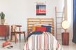Striped sheets on wooden bed between ladder and chair in retro bedroom interior with poster. Real photo