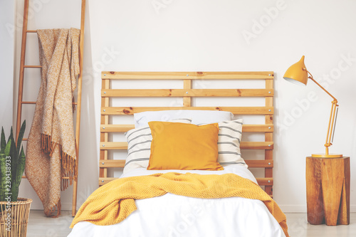 Leinwandbild Motiv Yellow cushions on wooden bed with blanket in bedroom interior with lamp, plant and ladder. Real photo