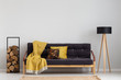 Log of wood next to comfortable sofa with yellow blanket and pillows, stylish wooden lamp with black lampshade, real photo copy space on the empty grey wall - 230439109