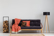 Log of wood next to comfortable sofa with strawberry red blanket and pillows, stylish wooden lamp with black lampshade, real photo copy space on the empty grey wall