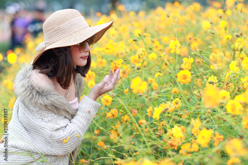 Leinwandbild Motiv cute and beautiful girl with hat standing in nature outdoors among cosmos flowers field (rest time on vacation concept)