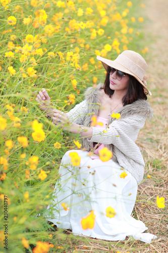 Leinwanddruck Bild cute and beautiful girl with hat standing in nature outdoors among cosmos flowers field (rest time on vacation concept)