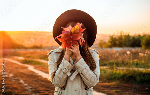Foto Murales Beauty Romantic Girl Outdoors enjoying nature holding leaves in hands. Beautiful autumn model with waving glow hair. Sun light