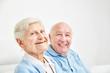 Leinwanddruck Bild - Glückliches Rentner Paar sitzt auf dem Sofa
