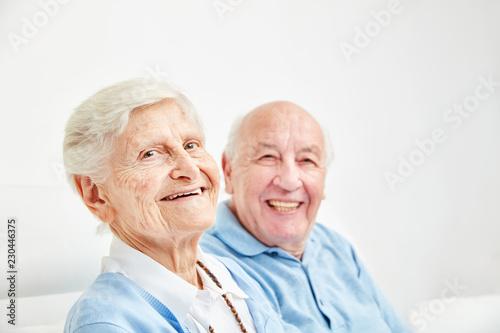 Leinwanddruck Bild Glückliches Rentner Paar sitzt auf dem Sofa