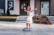 Feel amazing. Beaming dark-haired girl with nice hairstyle wearing little crown feeling amazing skateboarding