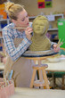 woman decorating head in pottery class