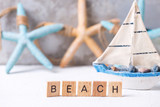 Word beach  from wooden blocks, sea stars  and boat toy against grey wall. - 230456909