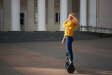 Young beautiful athletic fit girl riding on hoverboard in the street