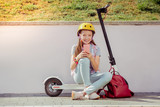 Red backpack. Kind red-haired girl keeping smile on face while sitting on her cycle