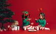 Kids eating cookies sitting beside a christmas tree