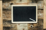 Empty black chalkboard with white chalk on brown, rustic wooden wall - 230470570