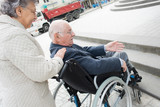 an old woman is pushing husband in wheelchair - 230473902