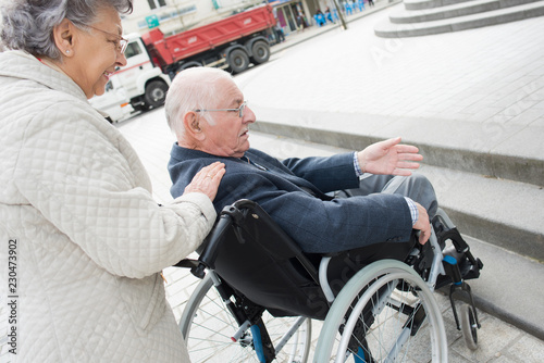 Foto Murales an old woman is pushing husband in wheelchair